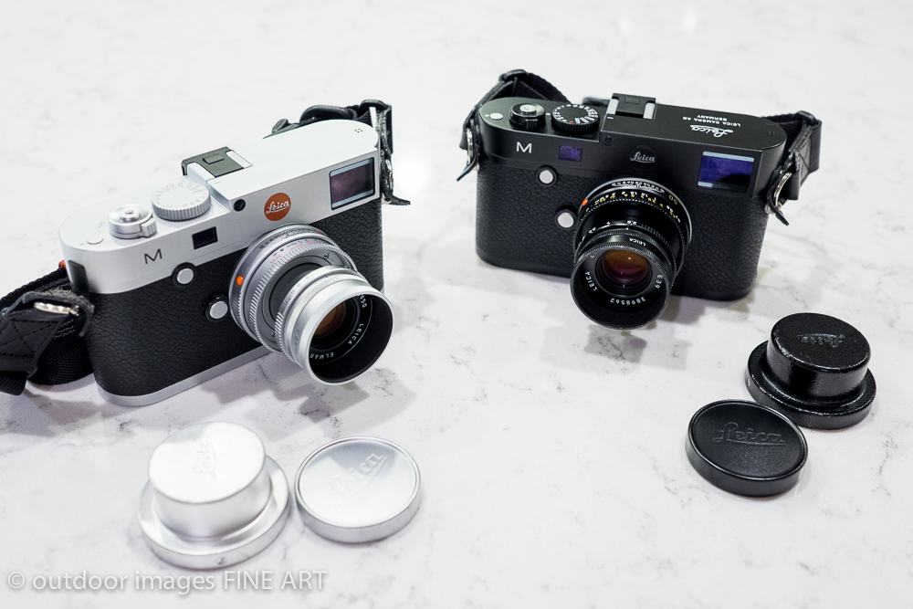 Black and Silver, both with a Leica Elmarit-M 50mm f/2.8 Collapsable including Leitz deep rear lens cap, sun shade and front lens cap.  Notice the Black Leica M has unique engraving and a black Leica dot.